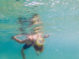 Child wearing snorkeling mask diving underwater
