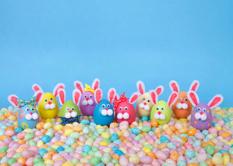 Craft Easter Bunnies made from plastic eggs standing in pastel jelly beans with a light blue background. Fun Easter line up with copy space