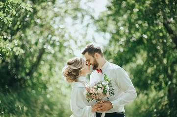 stylish bride in silk dress and groom in suit walking in sunny garden on wedding day. luxury wedding couple, happy newlyweds family. romantic moments.