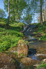 Stream and a waterfall in a ravine at summer