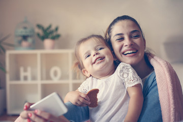 Cheerful mother and smiling girl taking self picture at home.