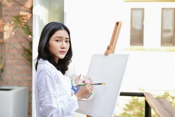Concept Artist Beautiful girl. Beautiful women are creating art. Beautiful woman is painting happily. Young artist painting outside the house.