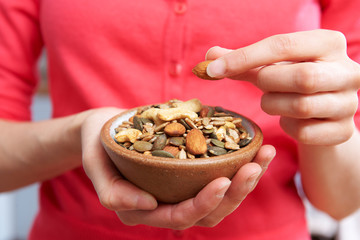 Close Up Of Woman Eating Bowl Of Healthy Nuts And Seeds