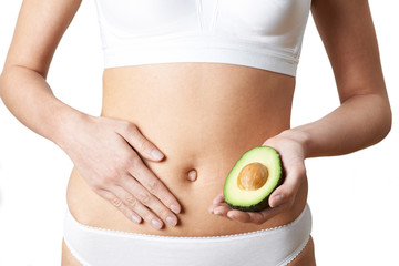 Close Up Of Woman In Underwear Holding Avocado And Touching Stomach