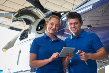 Portrait Of Aero Engineer And Apprentice Working On Helicopter In Hangar Looking At Digital Tablet