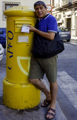 Men pokes a letter into a mailbox in Spain
