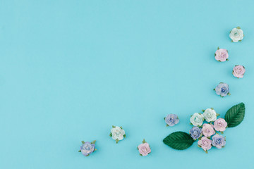 Blue tone paper flowers and green leaves on pastel blue background with copy space