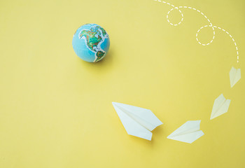 Paper airplane with globe on yellow paper background.