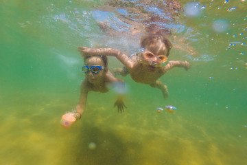 Two boys dive in swimming goggles in the sea
