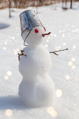 miniature snowman with a bucket on his head stands on a brightly lit snow in anticipation of spring.