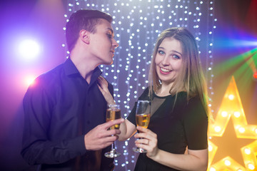 Three young men and two women  with glass champagne celebrate a birthday have fun in a nightclub