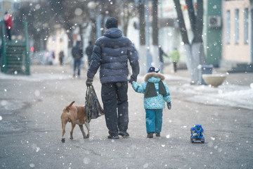 Father and little kid on the street in winter