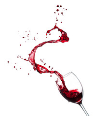 Red wine splashing from glass on white background