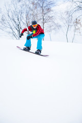 Picture of athlete in helmet with snowboard riding in snowy resort