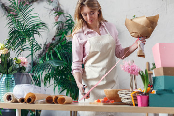 Picture of blonde florist in apron with bouquet at table with paper, marmalade, boxes