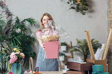 Picture of florist with floral composition in box at table with boxes, paper