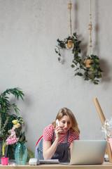 Image of florist woman talking on phone in flower shop