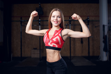 Photo of sports woman showing biceps