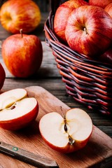 red ripe apples in a basket on a wooden background