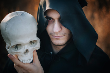 Halloween image. A handsome guy in a black cloak with a staff from a human skull against the background of a yellow field. Fantasy