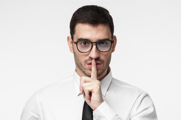 Studio picture of young business man isolated on grey background, pressing index finger to lips as if asking other to keep silent about secret or data