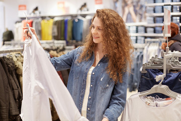 Photo of pleased female shopaholic chooses clothes for party, holds shirt on hangers, going to buy new outfit in shopping mall, spends salary on clothing. People, consumerism, buying concept