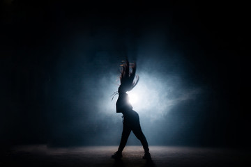 young woman dancing at night club on bright stage.loose hair.dancing on rock music. rock fan. disco party