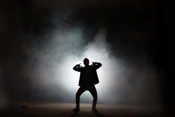 young rapper dancing isolated on black background