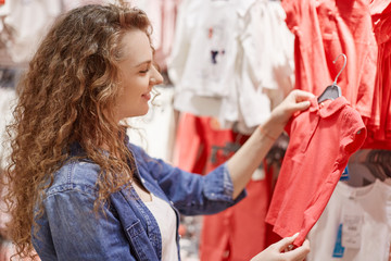 Sideways shot of curly young mother chooses t shirt for her little daughter, being in good mood as likes shopping, sees much stylish clothes on hangers. Pretty woman spends free time in clothes shop