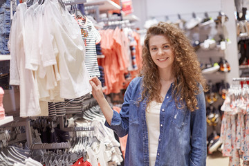 Indoor shot of stylish pleased curly young woman wears jean jacket, poses against shopping centre background with much garment, chooses new outfit for special occasion. Consumerism concept