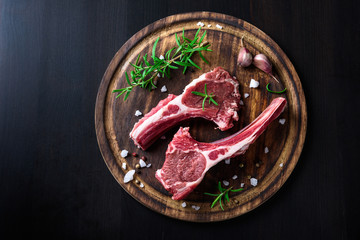 Two raw lamb chops on a wooden cutting board with spices on a dark wooden background