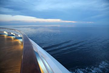 Twlight over a cruise ship deck, sailing across the calm ocean.