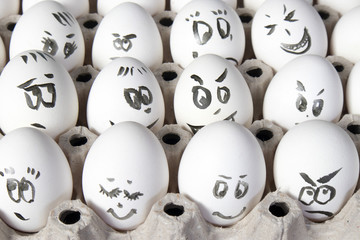 the Hen eggs in box. Eggs cover with drawings. Look like man face