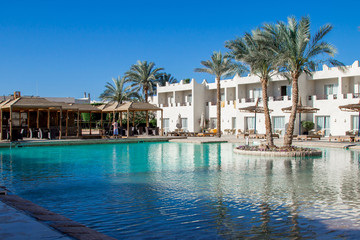 Hotel facade in sharm el sheikh with a deeep blue water in the swimming pool and palm trees, peaceful landscape