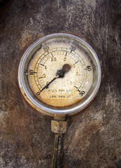 Old rusty round industrial pressure gauge with numbers round the dial mounted on a metal surface of a large abandoned diesel powered generator