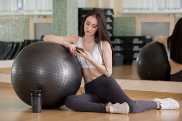Happy sporty young beautiful girl with smartphone listening to music while sitting near with fitness ball