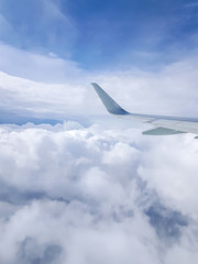 Photo of airplane wing, cloudy sky from porthole
