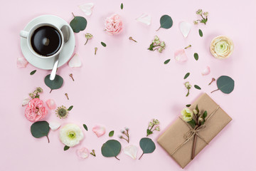 Workspace. Gift, cup of coffee and rose flowers. Flat lay, top view, copy space