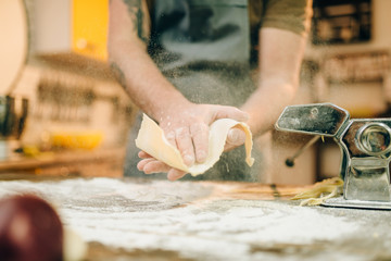 Male chef cooking dough and prepares pasta machine