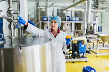 Worker at bottling factory checking juice quality.