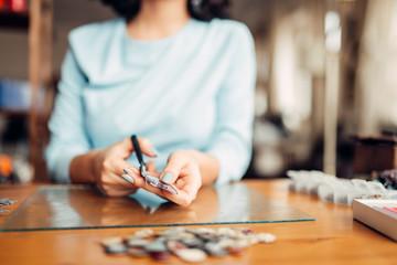 Female hands with scissors, handmade jewelry
