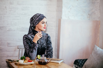 beautiful muslim woman writing on paper at cafe