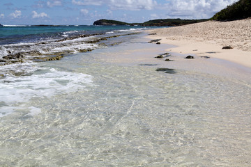 Crystal clear ripples of water lapping on sandy beach, Guadeloupe, Lesser Antillers, Caribbean