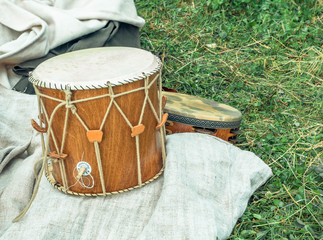 Percussion instruments drum leather and timbrel on a grass backgrond