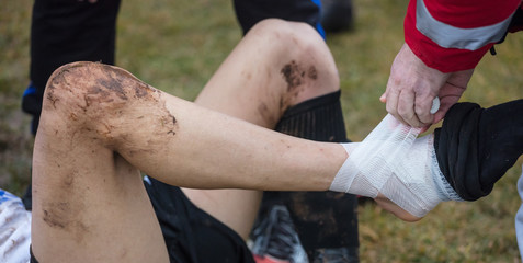 Soccer, football concept. Injured footballer lay down on field with hurting ankle. Blurred background, close up view.