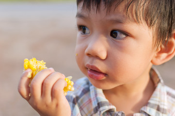 Cute a Little Asian Boy eating corn.