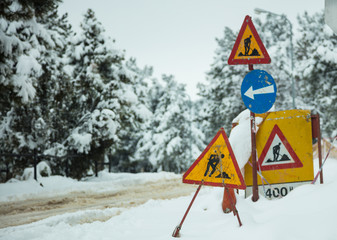 Under construction signs in snow. Snowy road and forest background.