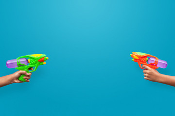 Hands holding plastic water gun on blue background