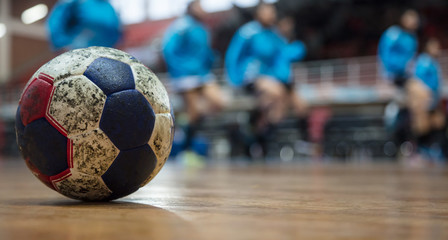 Handball ball on floor. Blurred exercising team background. Space for text.