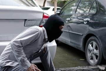Thief in black balaclava trying to break into car